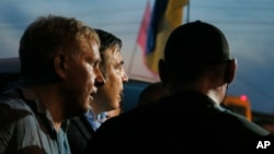 Former Georgian president and ex-governor of Ukraine's Odessa region Mikheil Saakashvili, center, is surrounded by supporters at Shehini checkpoint on Ukraine's border with Poland, in Shehini Ukraine, Sept. 10, 2017. Saakashvili and a crowd of supporters proceeded into Ukraine on foot after breaking through a line of border guards.