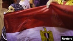 A girl holds Egypt's flag as she attends a sit-in protest organized by supporters of the deposed Egyptian President Mohamed Morsi, Cairo, July 11, 2013.