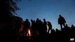 Para migran menghangatkan diri dekat api unggun sementara menunggu masuk ke kamp di Spielfeld, Austria (25/10). (AP/Petr David Josek)