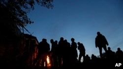 Di dân sưởi ấm tại một trại tị nạn ở thị trấn Spielfeld, Áo, ngày 25/10/2015.