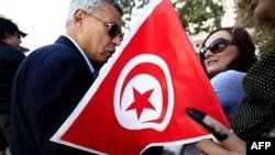 Một phụ nữ Tunisia cầm lá cờ quốc gia với ngón tay còn dấu mực, sau khi bà bỏ phiếu ở một phòng đầu phiếu trong thủ đô Tunis