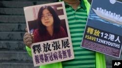 Một nhà hoạt động vì dân chủ cầm áp phích với hình của nhà báo Trung Quốc Zhang Zhan bên ngoài văn phòng liên lạc chính phủ trung ương tại Hong Kong, phàn đối án tù 4 năm dành cho cô vì tội tường trình virus corona bùng phát lúc đầu tại Vũ Hán.