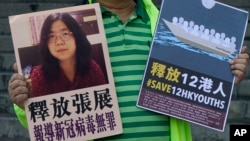 A pro-democracy activist holds placards with the picture of Chinese citizen journalist Zhang Zhan outside the Chinese central government's liaison office, in Hong Kong, Monday, Dec. 28, 2020.