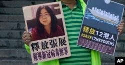 一名香港民主活动人士在中联办外手持上海维权人士、公民记者张展的照片。(2020年12月28日)