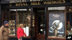 "In this picture taken on Saturday, May 28, 2016, a man and a woman pass a whisky shop on the ""Royal mile"" in Edinburgh, Scotland. Scotch Whisky Distillers, small and large, are very supportive of the UK's membership of the European Union. Scotch Whisky is Scotland's biggest export, supporting about 40,000 jobs in Scotland."