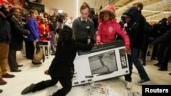 """Para pembeli saling berebut televisi pada hari """"Black Friday"""" di sebuah toko di London. Toko-toko di Inggris dibanjiri diskon pada hari Jumat pasca Thanksgiving, mengikuti tradisi promosi Black Friday di Amerika."""