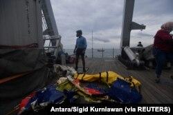 TNI AL berdiri di dekat kantong jenazah yang diyakini sebagai sisa-sisa pesawat Sriwijaya Air Flight SJ182 yang jatuh ke laut di Jakarta, 10 Januari 2021. (Foto: Antara/Sigid Kurniawan via REUTERS)