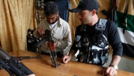 A member of the Free Syrian Army checks a weapon before buying it inside a shop in the al-Myassar neighborhood of Aleppo, May 20, 2013.