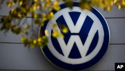 FILE - The VW sign of Germany's car company Volkswagen is displayed at a company retailer in Berlin, Germany. Volkswagen has agreed to pay its U.S. dealers $1.2 billion in its emissions cheating scandal.