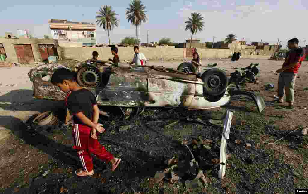 Residents gather at the site of a car bomb attack in Mahmudiya, south of Baghdad, Iraq July 23, 2012.
