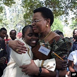 Graca Machel, wife to former South African president Nelson Mandela, centre right, hugs Charelen Vhuta, during her visit to Harare, Zimbabwe, 16 Nov 2010