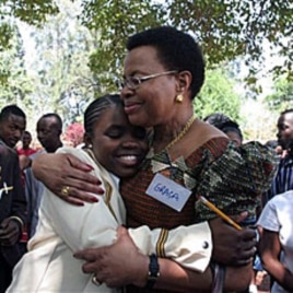 Graca Machel, wife to former South African president Nelson Mandela, centre right, hugs Charelen Vhuta, during her visit to Harare, Zimbabwe, 16 Nov 2010