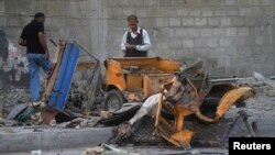 Members of a bomb disposal squad survey the site of a bomb blast outside a mosque in Karachi, Pakistan, June 5, 2014.