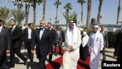 PM Palestina Ismail Haniyeh menyambut Emir Qatar Sheikh Hamad bin Khalifa al-Thani (kanan depan) saat tiba di Rafah, Jalur Gaza Selasa (23/10).