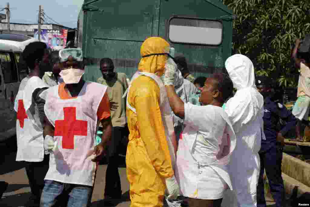 A health worker fixes another's protective suit in the Aberdeen district of Freetown, Sierra Leone, Oct. 14, 2014.