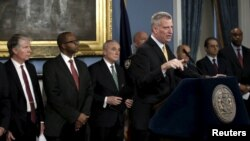 New York City Mayor Bill de Blasio, accompanied by local, state and federal law enforcement officials at Manhattan's City Hall, speaks to reporters about the establishment of special courts and a police unit dedicated to gun-related cases, Jan. 12, 2016.