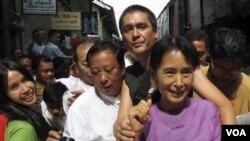 Aung San Suu Kyi bersama puteranya, Kim Aris (di belakang Suu Kyi) dan para pendukungnya di Yangon, Birma, 30 November 2010.