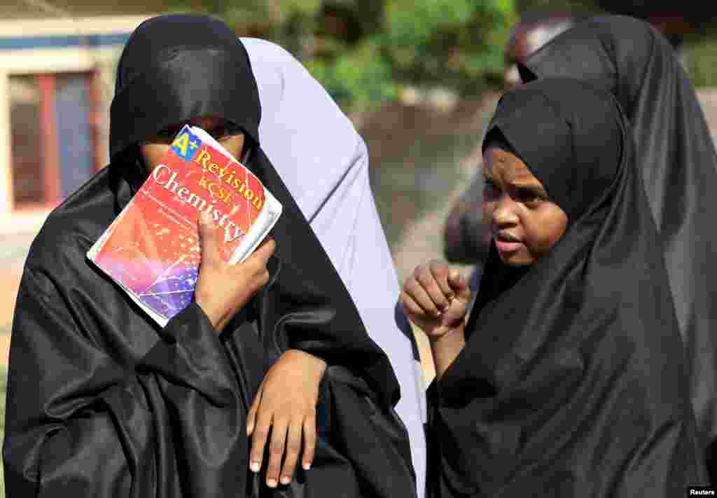 A student shields her face with a book at the main entrance of Garissa campus, the site of Thursday's attack by gunmen, in Garissa, April 3, 2015.