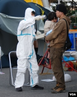 A man and a child are checked for radiation exposure in Fukushima in wake of the reactor meltdowns, March 13, 2011. (S. Herman/VOA)