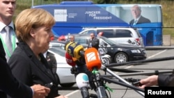 Germany's Chancellor Angela Merkel speaks near a promotional campaign bus of candidate for the European Commission presidency Jean-Claude Juncker as she arrives at an European People's Party meeting in Kortrijk, June 26, 2014.