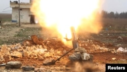 FILE - A Free Syrian Army fighter fires a shell toward Islamic State fighters in the northern Aleppo countryside, Syria.