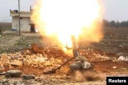 FILE - Free Syrian Army fighter fires a shell towards Islamic State fighters in the northern Aleppo countryside, Syria.