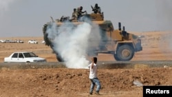 A protester throws stones at an armored army vehicle during a pro-Kurdish demonstration in solidarity with people of Kobani, near the Mursitpinar border crossing on the Turkish-Syrian border, in the Turkish town of Suruc in southeastern Sanliurfa province