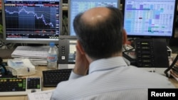 A trader looks at his screens during a bond auction on a trading floor in Madrid, June 7, 2012.