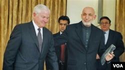 Menhan AS Robert Gates (kiri) dan Presiden Afghanistan Hamid Karzai di Kabul, 8 Desember 2010. Militer AS mengevaluasi kontrak dengan perusahaan-perusahaan Afghanistan.