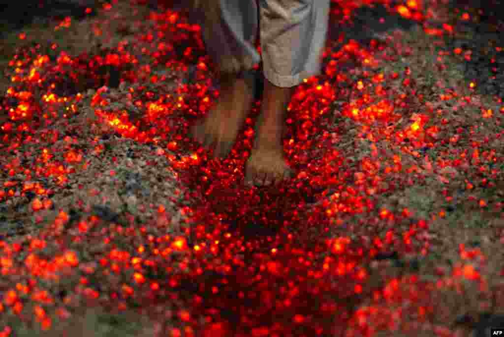 A Shi'ite Muslim walks on fire at a ceremony during the Ashura festival at a mosque in central Yangon December 16. (Soe Zeya Tun/Reuters)