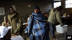 A Lesotho man wearing a traditional blanket prepares to vote at the Mpho primary school in Maseru, Lesotho, May 26, 2012.