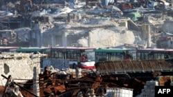 2016年12月18日,运送被困民众和抵抗部队的车辆通过阿勒颇南郊政府控制区。