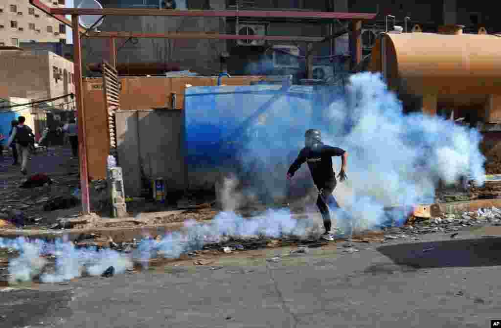 روز چهارشنبه نیز اعتراضات در شهر بغداد ادامه داشت. عکس از فرار یک معترض از گاز اشک آور در حوالی میدان الخلانی است.