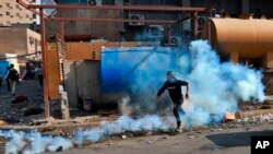 Seorang pengunjuk rasa anti-pemerintah diatasi dengan gas air mata yang ditembakkan oleh polisi anti huru hara selama bentrokan, di Khilani Square, Baghdad, Irak, Rabu, 13 November 2019. (Foto: AP/Khalid Mohammed)
