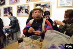90多歲的香港市民黃伯「 剥花生」看特首選舉電視辯論直播。(美國之音湯惠芸攝)
