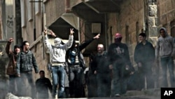 Anti-Syrian government protesters flash V sign as they protest in the southern city of Daraa, March 23, 2011.
