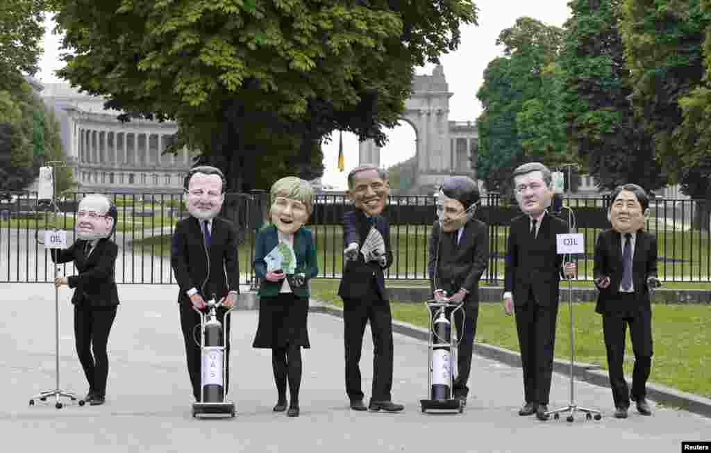 Oxfam's activists wear masks depicting leaders of the G7 countries outside the European Council in Brussels, Belgium.   The masks represent, from left, French President Francois Hollande, British Prime Minister David Cameron, German Chancellor Angela Merkel, U.S. President Barack Obama, Italian Prime Minister Matteo Renzi, Canadian Prime Minister Stephen Harper and Japanase Prime Minister Shinzo Abe.