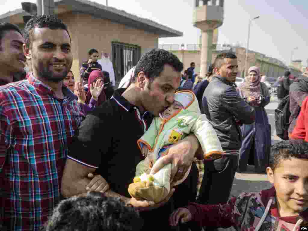 Galal Araby kisses his 11 month-old son after after being released from Tora prison in Cairo, Egypt, Tuesday, March 14, 2017. Galal was sentenced to five years in jail. He only served 18 months. (H. Elrasam/VOA)