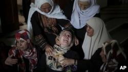 សាច់ញាតិក្រុមសកម្មប្រយុទ្ធហាម៉ាស៥នាក់ដែលបានស្លាប់យំក្នុងពិធីបុណ្យសពរបស់សមាជិកគ្រួសារខ្លួននៅភាគខាងជើងតំបន់Gazaនៅថ្ងៃទី៩កក្កដាឆ្នាំ២០១៤។(AP Photo/Khalil Hamra)