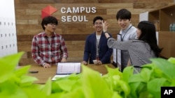 FILE - Employees of Dable, a startup and ventures investor, stand around a table during a media tour at the Google campus in Seoul, South Korea, May 8, 2015.