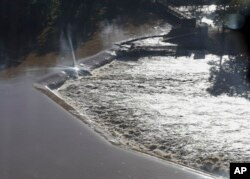Floodwaters rush over a diversion dam in Columbia, S.C., Oct. 6, 2015. Despite an improving forecast, it will still take weeks for the state to return to normal after being pummeled by a historic rainstorm.