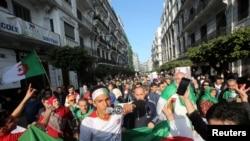 2020年2月14日,阿尔及利亚首都的抗议者手举国旗游行示威,纪念一年前的大规模抗议,要求进行彻底的政改,铲除腐败。