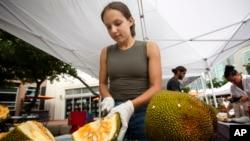 Sara Diaz, from LNB Groves, cuts a jackfruit at the Monday night green market in downtown Miami, Monday, June 8, 2015. (AP Photo/J Pat Carter)