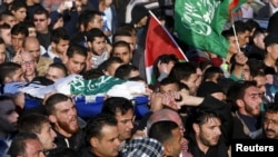Mourners carry the body of 22-year-old Palestinian, Oday Ersheid, who was shot and killed by Israeli troops during clashes on Friday, during his funeral in the West Bank city of Hebron, December 11, 2015.