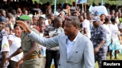 Incumbent President Faure Gnassingbe, who is running for a third term, waves to a crowd at a campaign rally in Tado, Togo, April 13, 2015.