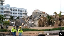 Workers walk past the collapsed and subsequently demolished Champlain Towers South condominium building, Tuesday, July 6, 2021, in Surfside, Fla. (AP Photo/Lynne Sladky)