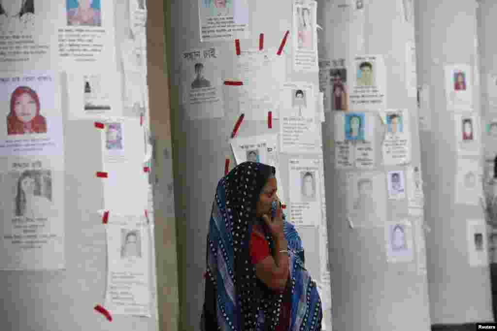 A woman waits for news of her relative, a garment worker, who is missing after the collapse of Rana Plaza building, in front of missing people posters in Savar, Bangladesh, April 30, 2013.