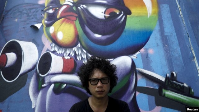 Thai graffiti artist Asin Acid poses near his graffiti in Bangkok, Thailand, March 7, 2016.