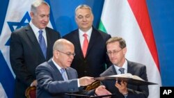 Staying on a four-day official visit in Hungary, Israeli Prime Minister Benjamin Netanyahu, rear left, and his Hungarian counterpart Viktor Orban, rear right, look on as Israeli Ambassador Yosef Amrani, left, and Hungarian Minister of National Economy Mihaly Varga sign a declaration on cooperation in the field of innovation between the two countries in the Parliament building in Budapest, Hungary, July 18, 2017.