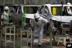 FILE - Employees work in the new multibillion-dollar Honda car plant in Celaya, in the central Mexican state of Guanajuato, Feb. 21, 2014.